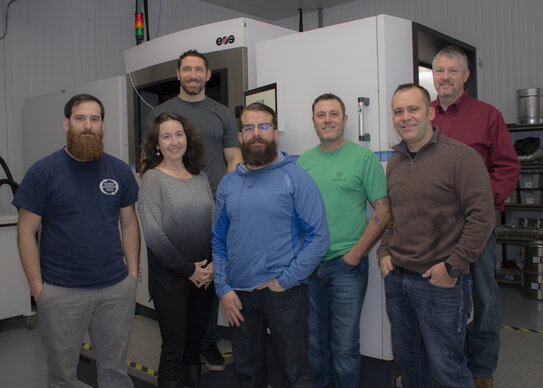 Integrated 3D Manufacturing (i3D) team in front of their new EOS M 400-4 DMLS system, expanding their metal AM production machines to seven.